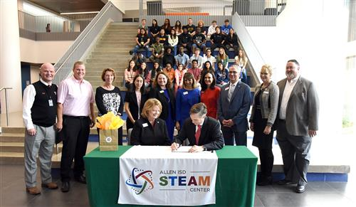 Rep. Taylor signs the proposed legislation at the Allen ISD STEAM Center.